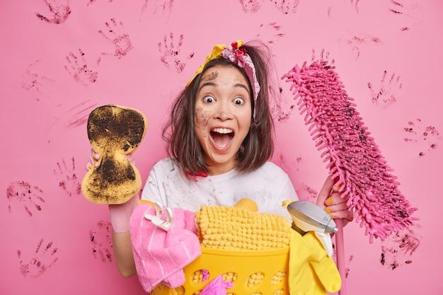 Huisvrouw roept luid wrijft stof in kamer houdt vuile spons vast en dweil doet was ruimt huis poseert op roze
