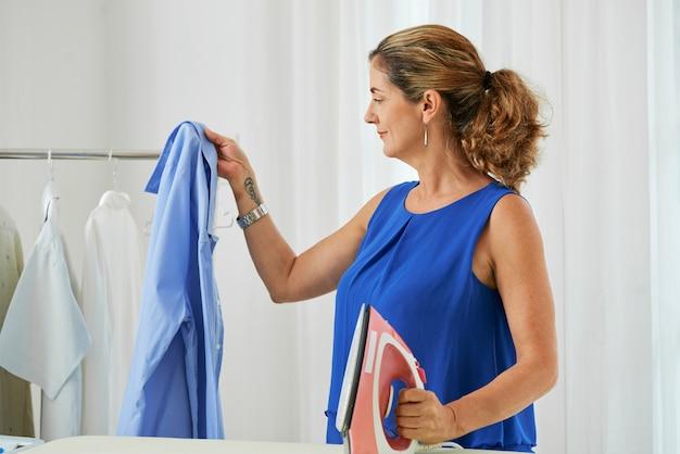 Huisvrouw strijken van kleding