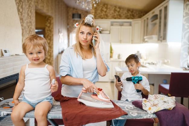 Huisvrouw telefoneert, kinderen dollen in de keuken. vrouw met kinderen die thuis samen spelen. vrouwelijke persoon met dochter en zoon in hun huis