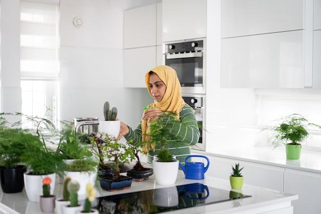 Huisvrouw thuis planten in de keuken water geven