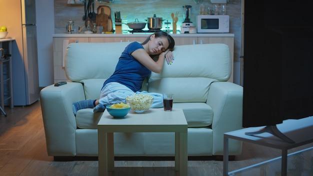 Huisvrouw valt in slaap in de woonkamer op de bank voor tv. moe uitgeputte eenzame slaperige dame in pyjama slapen op comfortabele bank in woonkamer, ogen sluiten terwijl ze 's nachts tv kijken