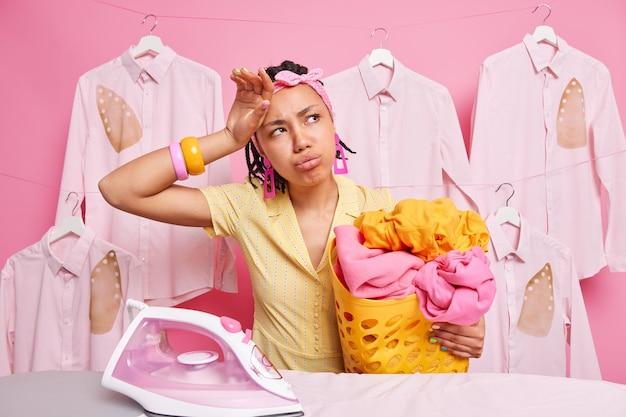 Huisvrouw veegt voorhoofd is vermoeid gezichtsuitdrukking veegt voorhoofd af houdt mand vol wasgoed moet op tijd klaar zijn met huishoudelijk werk denkt aan iets poseert op gestreken kleding aan hangers