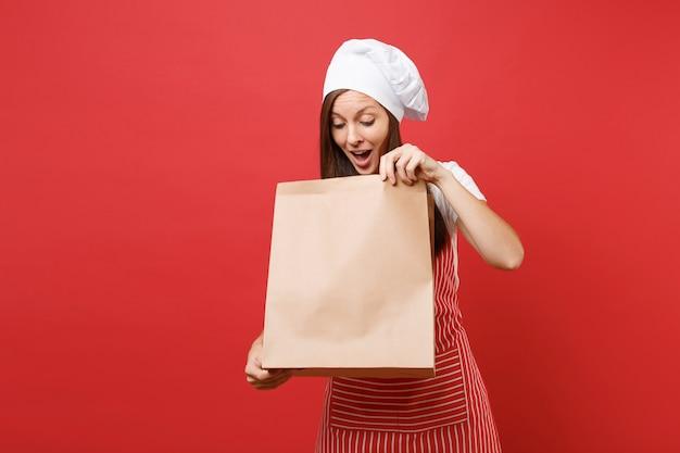 Huisvrouw vrouwelijke chef-kok bakker in gestreepte schort t-shirt toque chef-koks hoed geïsoleerd op rode muur achtergrond vrouw houd in de hand bruin duidelijk leeg leeg ambachtelijke papieren zak afhaalmaaltijden mock up kopie ruimte concept