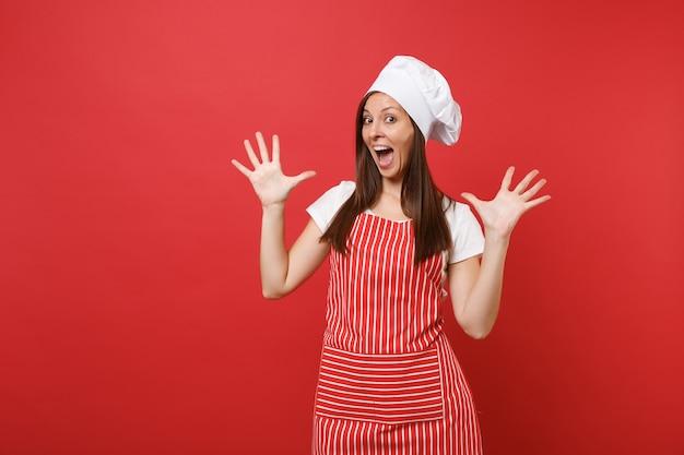 Huisvrouw vrouwelijke chef-kok bakker in gestreepte schort, wit t-shirt, toque chef-koks hoed geïsoleerd op rode muur achtergrond. geschokte gekke gekke huishoudstervrouw die handen uitspreidt. mock-up kopie ruimteconcept.