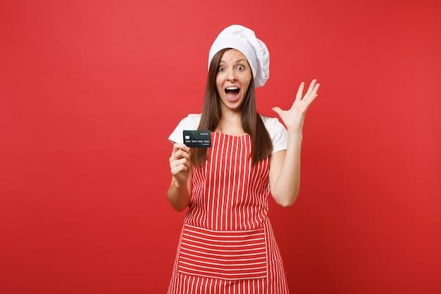 Huisvrouw vrouwelijke chef-kok bakker in gestreepte schort wit t-shirt toque chef-koks hoed geïsoleerd op rode muur achtergrond. opgewonden vrouw houdt creditcard in de hand, geldloos geld. mock-up kopie ruimte concept