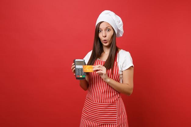 Huisvrouw vrouwelijke chef-kok of bakker in gestreepte schort t-shirt toque chef-koks hoed geïsoleerd op rode muur achtergrond. vrouw houdt in de hand bankbetaalterminal creditcard nfc-apparaat mock-up kopie ruimteconcept