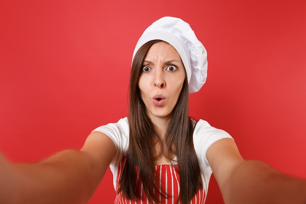 Huisvrouw vrouwelijke chef-kok of bakker in gestreepte schort, wit t-shirt, toque chef-koks hoed geïsoleerd op rode muur achtergrond. close-up huishoudster vrouw doen selfie schot te nemen. mock-up kopie ruimteconcept.