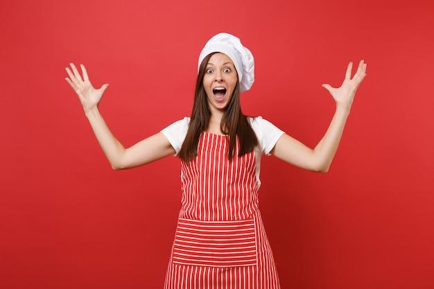 Huisvrouw vrouwelijke chef-kok of bakker in gestreepte schort, wit t-shirt, toque chef-koks hoed geïsoleerd op rode muur achtergrond. gelukkige expressieve huishoudstervrouw die handen uitspreidt. mock-up kopie ruimteconcept.