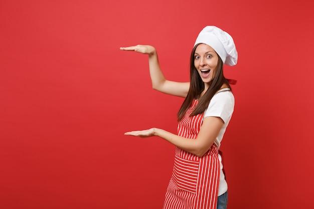 Huisvrouw vrouwelijke chef-kok of bakker in gestreepte schort, wit t-shirt, toque chef-koks hoed geïsoleerd op rode muur achtergrond. gelukkige huishoudster vrouw gebaren demonstreren grootte. mock-up kopie ruimteconcept.