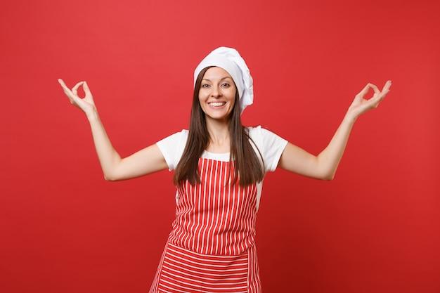 Huisvrouw vrouwelijke chef-kok of bakker in gestreepte schort wit t-shirt, toque chef-koks hoed geïsoleerd op rode muur achtergrond. glimlachende huishoudster vrouw hand in hand in yoga gebaar. mock-up kopie ruimteconcept.
