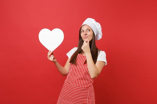Huisvrouw vrouwelijke chef-kok of bakker in gestreepte schort, wit t-shirt, toque chef-koks hoed geïsoleerd op rode muur achtergrond. glimlachende huishoudster vrouw houdt lege hart werkruimte. mock-up kopie ruimteconcept.