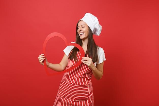 Huisvrouw vrouwelijke chef-kok of bakker in gestreepte schort, wit t-shirt, toque chef-koks hoed geïsoleerd op rode muur achtergrond. glimlachende huishoudstervrouw die houten rood hart houdt. mock-up kopie ruimteconcept.