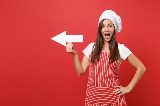 Huisvrouw vrouwelijke chef-kok of bakker in gestreepte schort, wit t-shirt, toque chef-koks hoed geïsoleerd op rode muur achtergrond. glimlachende leuke huishoudstervrouw die kant met pijl toont. mock-up kopie ruimteconcept.