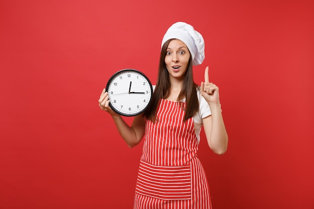 Huisvrouw vrouwelijke chef-kok of bakker in gestreepte schort, wit t-shirt, toque chef-koks hoed geïsoleerd op rode muur achtergrond. glimlachende vrouw die de klok rond in de hand houdt, schiet op. mock-up kopie ruimteconcept.