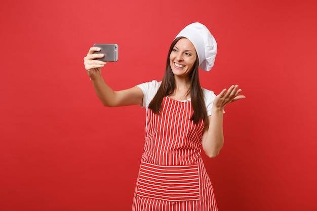 Huisvrouw vrouwelijke chef-kok of bakker in gestreepte schort, wit t-shirt, toque chef-koks hoed geïsoleerd op rode muur achtergrond. lachende leuke vrouw doet selfie schot op mobiele telefoon. mock-up kopie ruimteconcept.