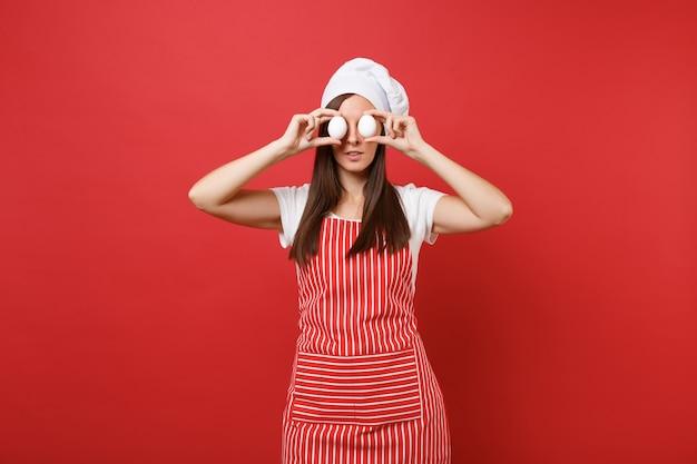 Huisvrouw vrouwelijke chef-kok of bakker in gestreepte schort, wit t-shirt, toque chef-koks hoed geïsoleerd op rode muur achtergrond. leuke huishoudster vrouw houdt in handen twee kippeneieren. mock-up kopie ruimteconcept.