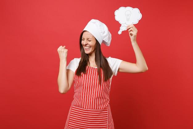 Huisvrouw vrouwelijke chef-kok of bakker in gestreepte schort wit t-shirt toque chef-koks hoed geïsoleerd op rode muur achtergrond. leuke huishoudster vrouw houdt zeg wolk met gloeilamp idee. mock-up kopie ruimte concept