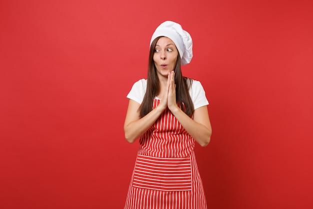 Huisvrouw vrouwelijke chef-kok of bakker in gestreepte schort wit t-shirt, toque chef-koks hoed geïsoleerd op rode muur achtergrond. leuke schattige huishoudster vrouw gevouwen armen in afwachting. mock-up kopie ruimteconcept.