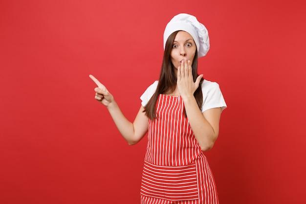 Huisvrouw vrouwelijke chef-kok of bakker in gestreepte schort, wit t-shirt, toque chef-koks hoed geïsoleerd op rode muur achtergrond. mooie huishoudster vrouw wijsvinger omhoog. mock-up kopie ruimteconcept.
