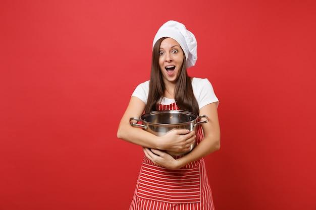 Huisvrouw vrouwelijke chef-kok of bakker in gestreepte schort wit t-shirt toque chef-koks hoed geïsoleerd op rode muur achtergrond. mooie huishoudstervrouw die lege aardewerkpot houdt. mock-up kopie ruimte concept