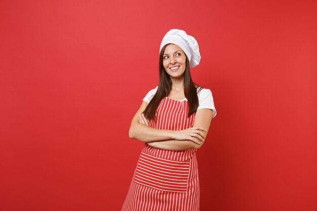 Huisvrouw vrouwelijke chef-kok of bakker in gestreepte schort, wit t-shirt, toque chef-koks hoed geïsoleerd op rode muur achtergrond. mooie jonge huishoudster vrouw hand in hand gekruist. mock-up kopie ruimteconcept.