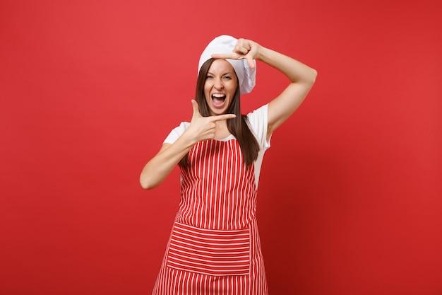 Huisvrouw vrouwelijke chef-kok of bakker in gestreepte schort, wit t-shirt, toque chef-koks hoed geïsoleerd op rode muur achtergrond. mooie leuke vrouw handen fotolijst gebaar maken. mock-up kopie ruimteconcept.