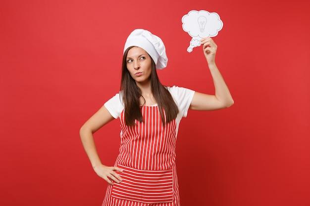 Huisvrouw vrouwelijke chef-kok of bakker in gestreepte schort wit t-shirt toque chef-koks hoed geïsoleerd op rode muur achtergrond. peinzende vrouw denkt, houd zeg wolk met gloeilampidee. mock-up kopie ruimteconcept.