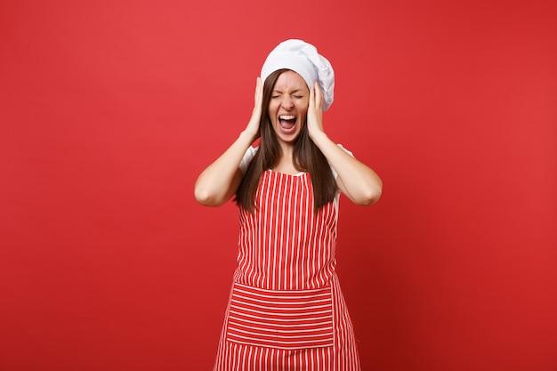 Huisvrouw vrouwelijke chef-kok of bakker in gestreepte schort, wit t-shirt, toque chef-koks hoed geïsoleerd op rode muur achtergrond. schreeuwende geschokte huishoudstervrouw legde handen op het hoofd. mock-up kopie ruimteconcept.