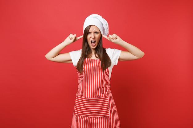 Huisvrouw vrouwelijke chef-kok of bakker in gestreepte schort, wit t-shirt, toque chef-koks hoed geïsoleerd op rode muur achtergrond. triest geschokte huishoudster vrouw bedek oren met vingers. mock-up kopie ruimteconcept.