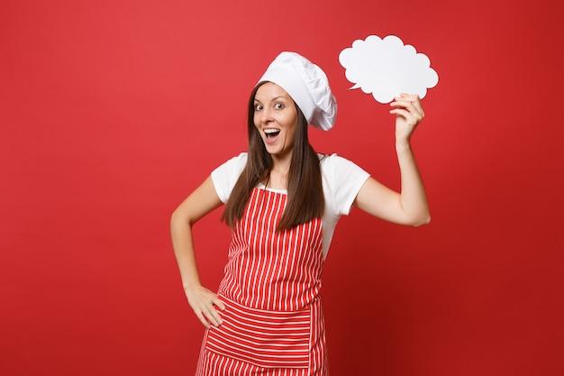 Huisvrouw vrouwelijke chef-kok of bakker in gestreepte schort wit t-shirt toque chef-koks hoed geïsoleerd op rode muur achtergrond. vrouw houd in de hand leeg leeg zeg wolk, tekstballon. mock-up kopie ruimteconcept.