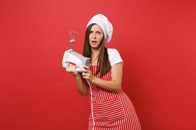 Huisvrouw vrouwelijke chef-kok of bakker in gestreepte schort wit t-shirt toque chef-koks hoed geïsoleerd op rode muur achtergrond. vrouw houdt keukenmixer vast, kook kerstgemberkoekje. bespotten kopie ruimte concept.