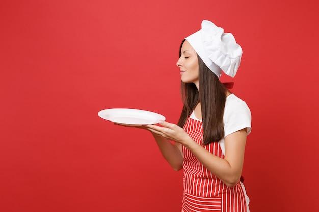 Huisvrouw vrouwelijke chef-kok of bakker in gestreepte schort, wit t-shirt, toque chef-koks hoed geïsoleerd op rode muur achtergrond. vrouw houdt lege lege ronde plaat met plaats voor voedsel. mock-up kopie ruimte concept