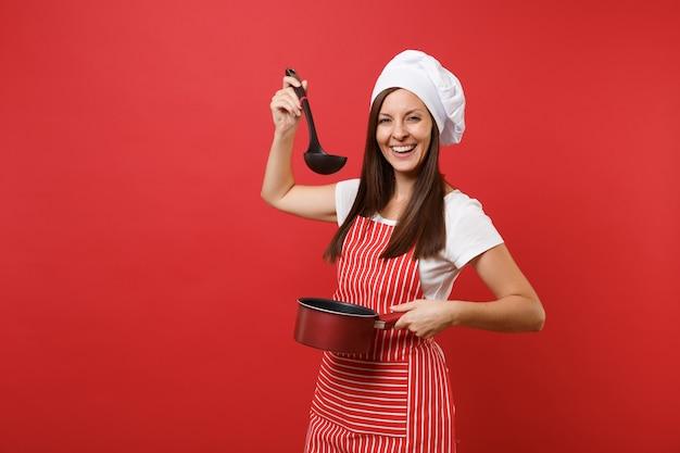 Huisvrouw vrouwelijke chef-kok of bakker in gestreepte schort wit t-shirt toque chef-koks hoed geïsoleerd op rode muur achtergrond. vrouw houdt proeverij lege kookpan zwarte soeplepel dipper. mock-up kopie ruimte concept