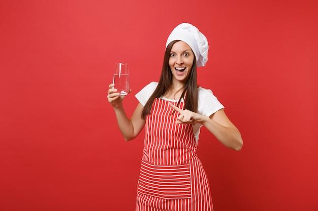 Huisvrouw vrouwelijke chef-kok of bakker in gestreepte schort wit t-shirt toque chef-koks hoed geïsoleerd op rode muur achtergrond. vrouw met helder vers zuiver water drinken uit glas. mock-up kopie ruimte concept