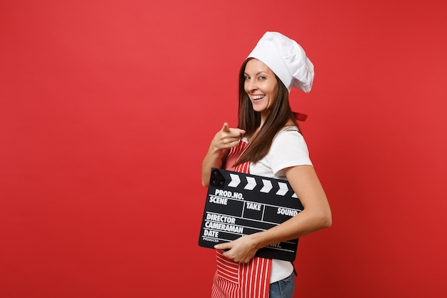 Huisvrouw vrouwelijke chef-kok of bakker in gestreepte schort, wit t-shirt, toque chef-koks hoed geïsoleerd op rode muur achtergrond. vrouw met klassieke zwarte film filmklapper maken. mock-up kopie ruimteconcept.