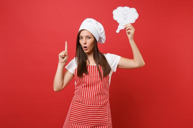 Huisvrouw vrouwelijke chef-kok of bakker in gestreepte schort wit t-shirt toque chef-koks hoed geïsoleerd op rode muur achtergrond. zelfverzekerde serieuze vrouw houdt het idee van een wolk gloeilamp. mock-up kopie ruimteconcept.