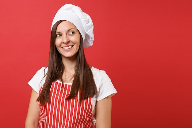 Huisvrouw vrouwelijke chef-kok of bakker in rood gestreepte schort, wit t-shirt, toque chef-koks hoed geïsoleerd op rode muur achtergrond. close-up portret van huishoudster brunette vrouw. bespotten kopie ruimte concept.