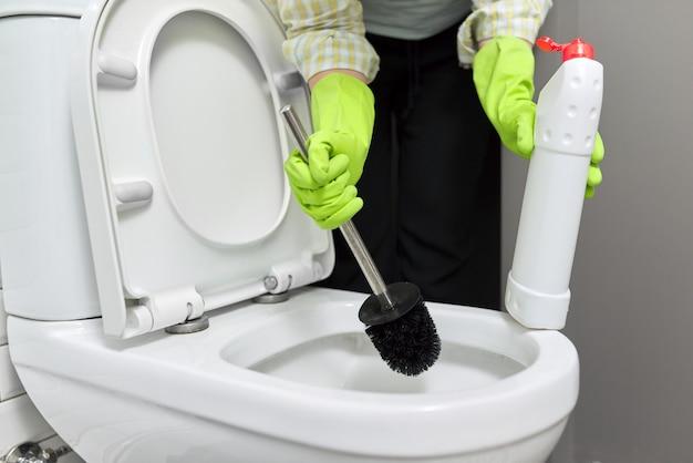 Huisvrouw wassen en desinfecteren toilet. vrouw in handschoenen met wasmiddel en borstel. huishouding, netheid thuis, huishoudelijke taken, service, mensenconcept