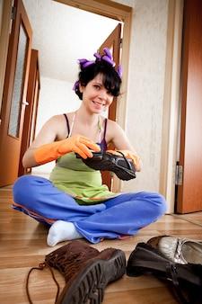 Huisvrouw zit op een vloer en maakt schoeisel schoon