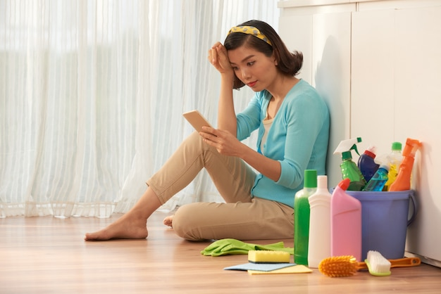 Huisvrouwenzitting op de keukenvloer die onderbreking van huishoudelijk werk nemen en smartphone gebruiken