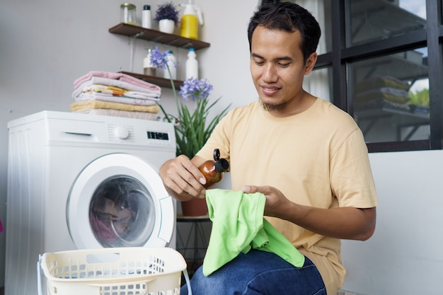Huiswerk. aziatische man thuis was doen. wat wasmiddel op de kleding aanbrengen