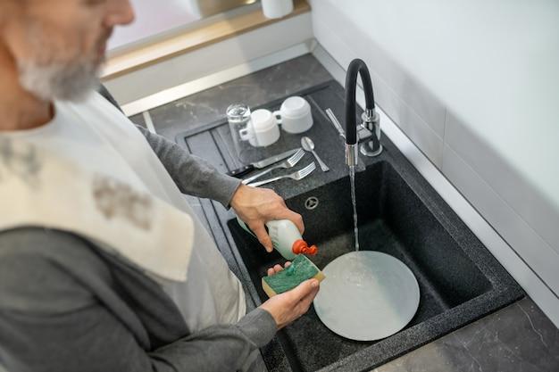 Huiswerk. close up van een man die de borden in de keuken wast