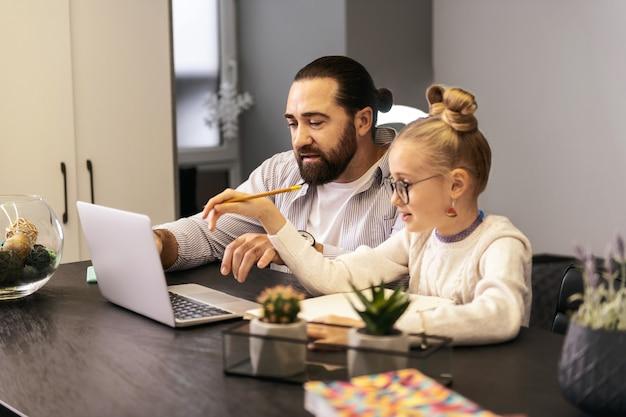 Huiswerk. donkerharige, bebaarde leraar in een gestreept overhemd die huistaak met zijn leerling doet