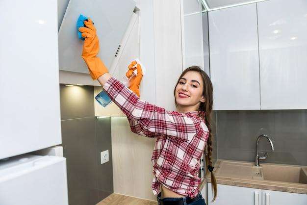 Huiswerk. jonge vrouw die haar keuken met doek en afwasmiddel schoonmaakt