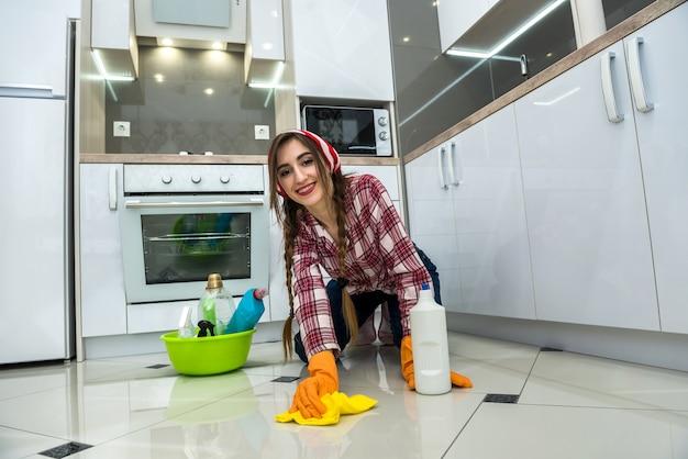 Huiswerk. jonge vrouw die haar keuken schoonmaakt met vod en afwasmiddel