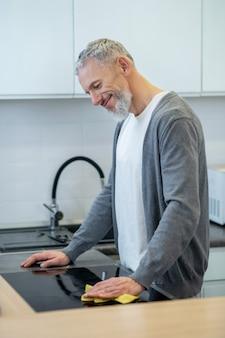 Huiswerk. man in huiskleding die de borden in de keuken afwast