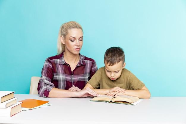 Huiswerk op afstand met moeder thuis in quarantaine. jongen met moeder aan het bureau zitten en studeren.
