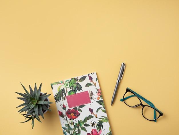 Huiswerk. zakelijke plat lag met opmerking, potlood, bril en sappig op gele achtergrond.