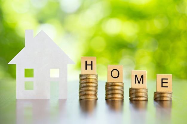 Huiswoord op muntstukkenstapel met groene achtergrond. sparen voor kopen huisconcept