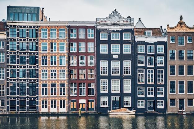 Huizen en boot op de amsterdamse gracht damrak met reflectie. ams